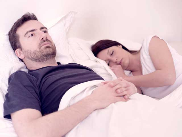 A man lying in bed thinking about the types of premature ejaculation