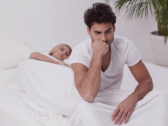A young man with erectile dysfunction sitting on the side of the bed