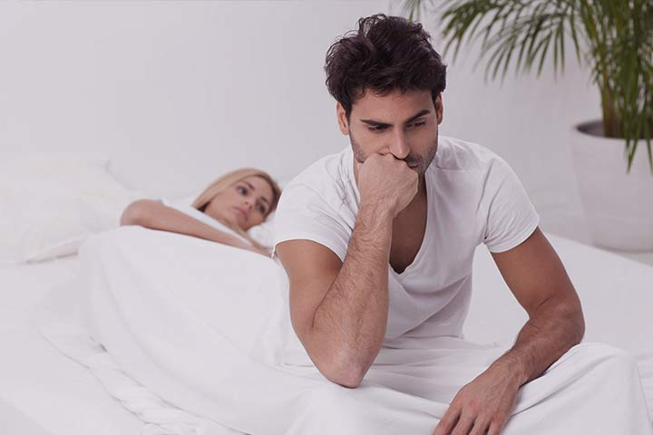A young men with erectile dysfunction sitting on the side of his bed