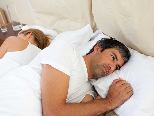 men in bed thinking about performance anxiety and erectile dysfunction