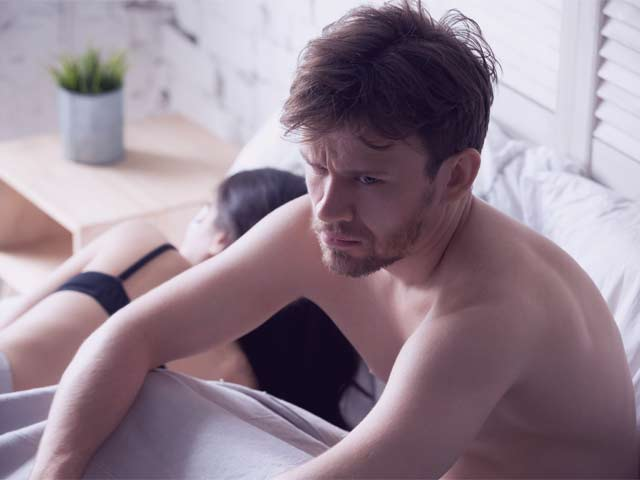 An image of a man sitting on the bed worried about having performance anxiety with his new partner