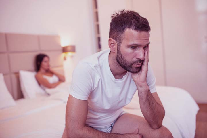 a disappointed man sitting in bed thinking about his low sex drive