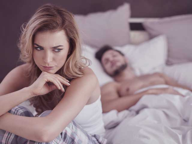 A woman in s sexless marriage sitting at bed disappointed from her husband